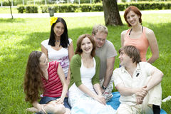 Groupe d'amis s'asseyant dans l'herbe Photo stock