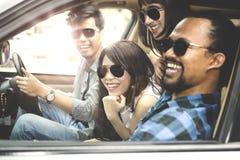 Groupe d'amis s'asseyant dans la voiture Photographie stock