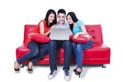 Groupe d'amis s'asseyant dans le sofa avec l'ordinateur portable Photos libres de droits