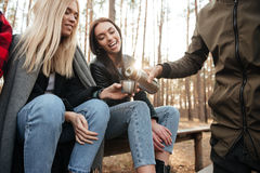 Groupe d'amis s'asseyant dehors dans le thé potable de forêt Images stock