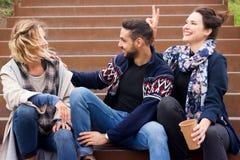 Groupe d'amis s'asseyant dehors sur des escaliers Image stock