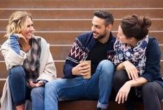 Groupe d'amis s'asseyant dehors sur des escaliers Photo libre de droits