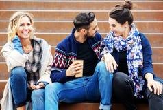 Groupe d'amis s'asseyant dehors sur des escaliers Images libres de droits