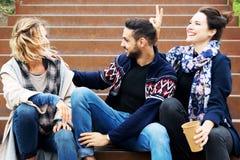 Groupe d'amis s'asseyant dehors sur des escaliers Image libre de droits