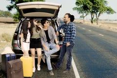 Groupe d'amis s'asseyant derrière la voiture ensemble Images libres de droits