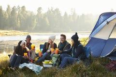 Groupe d'amis s'asseyant en dehors de leur tente près d'un lac Image stock