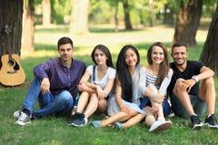 Groupe d'amis s'asseyant en parc sur l'herbe et regardant l'appareil-photo Images libres de droits