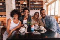 Groupe d'amis s'asseyant ensemble dans un café Images stock