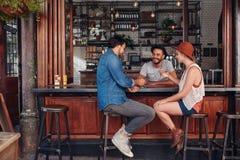 Groupe d'amis s'asseyant et parlant à un café Photos libres de droits