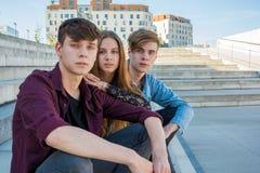 Groupe d'amis s'asseyant sur des escaliers dans la ville Images libres de droits