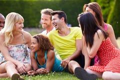 Groupe d'amis s'asseyant sur l'herbe ensemble Images stock