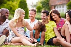 Groupe d'amis s'asseyant sur l'herbe ensemble Image libre de droits