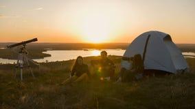 Groupe d'amis s'asseyant sur l'herbe près de la tente refroidissant au coucher du soleil Photographie stock libre de droits