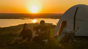 Groupe d'amis s'asseyant sur l'herbe près de la tente refroidissant au coucher du soleil Photos stock