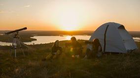 Groupe d'amis s'asseyant sur l'herbe près de la tente refroidissant au coucher du soleil Image libre de droits