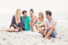 Groupe d'amis s'asseyant sur la plage avec la guitare Photo stock