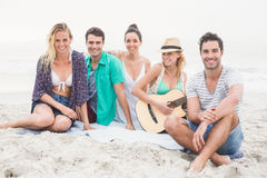 Groupe d'amis s'asseyant sur la plage avec la guitare Images libres de droits