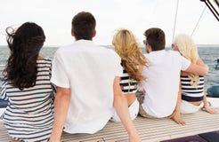 Groupe d'amis s'asseyant sur la plate-forme de yacht Photos libres de droits