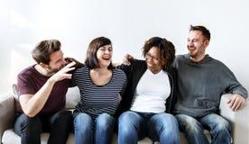 Groupe d'amis s'asseyant sur le divan Photographie stock