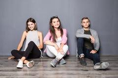 Groupe d'amis s'asseyant sur le plancher sur le fond gris Photo stock
