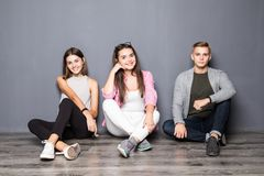 Groupe d'amis s'asseyant sur le plancher sur le fond gris Images libres de droits