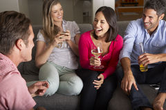 Groupe d'amis s'asseyant sur Sofa Talking And Drinking Wine Photo stock