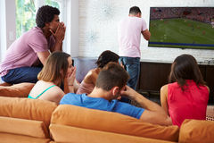 Groupe d'amis s'asseyant sur Sofa Watching Soccer Together Photo libre de droits