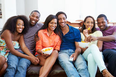 Groupe d'amis s'asseyant sur Sofa Watching TV ensemble Image libre de droits