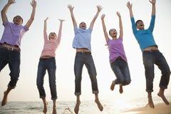 Groupe d'amis sautant à la plage, tir de Mid Air photographie stock libre de droits