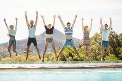 Groupe d'amis sautant au poolside Images libres de droits