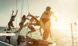 Groupe d'amis sautant dans l'eau du bateau Image stock