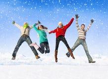 Groupe d'amis sautant dans la neige Photos stock