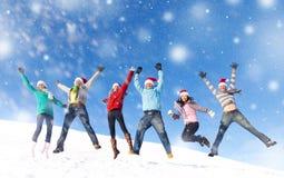 Groupe d'amis sautant dans la neige Photo libre de droits