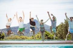 Groupe d'amis sautant dans la piscine Image stock