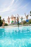 Groupe d'amis sautant dans la piscine Photo libre de droits