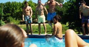 Groupe d'amis sautant dans la piscine banque de vidéos
