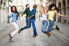 Groupe d'amis sautant ensemble dehors Photos libres de droits