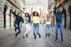 Groupe d'amis sautant ensemble dehors Images libres de droits