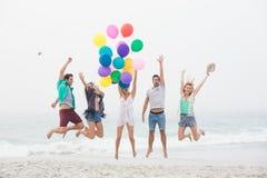Groupe d'amis sautant sur la plage avec des ballons Image libre de droits