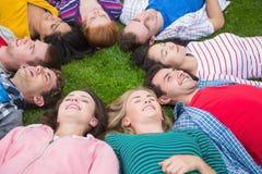 Groupe d'amis se couchant en parc Images libres de droits