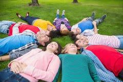 Groupe d'amis se couchant en parc Image stock