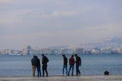 Groupe d'amis se réunissant au bord de la mer Images libres de droits