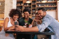 Groupe d'amis se réunissant au café utilisant le téléphone portable Image libre de droits