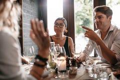 Groupe d'amis se réunissant au restaurant pour le dîner Images stock