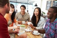 Groupe d'amis se réunissant dans le café Image stock