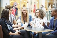 Groupe d'amis se réunissant dans le ½ de CafÅ de centre commercial Photo stock
