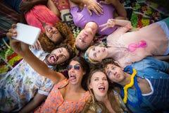 Groupe d'amis se situant en cercle et prenant un selfie Photo stock