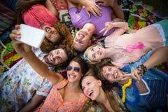 Groupe d'amis se situant en cercle et prenant un selfie Images stock