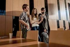 Groupe d'amis se tenant dans la chambre près du mur en bois et regardant l'écran de comprimé Images stock