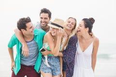 Groupe d'amis se tenant ensemble sur la plage Photo libre de droits